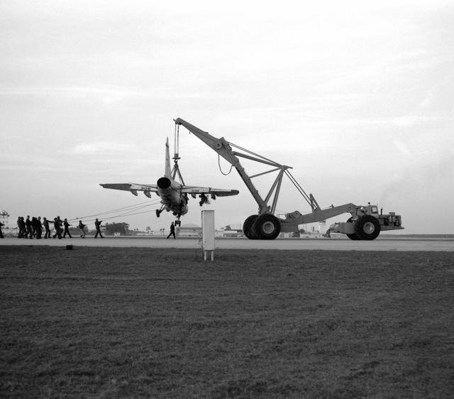 An aircraft crane is used to hoist an Attack Squadron 66 (VA-66) A-7E Corsair II aircraft during recovery operations. The aircraft suffered moderate damage to its undercarriage and structural damage to its main airframe when it made a crash landing