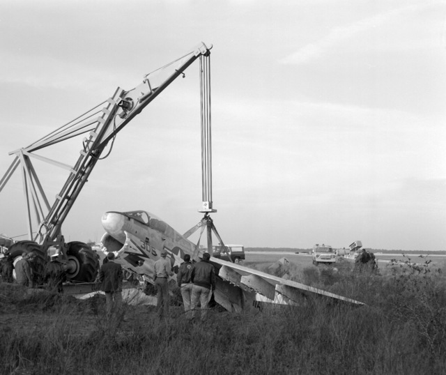 An aircraft crane is used to hoist an Attack Squadron 66 (VA-66) A-7E Corsair II during recovery operations. The aircraft suffered moderate damage to its undercarriage and structural damage to its main airframe when it made a crash landing