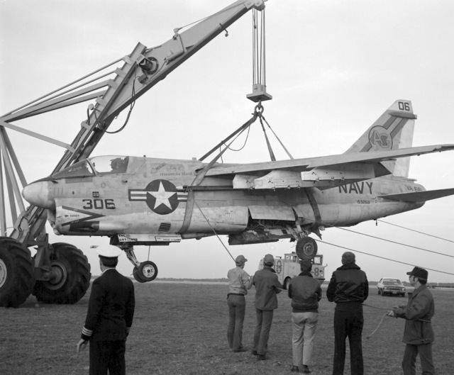 An aircraft crane is used to hoist an Attack Squadron 66 (VA-66) Corsair II during recovery operations. The aircraft suffered moderate damage to its undercarriage and structural damage to its main airframe when it made a crash landing