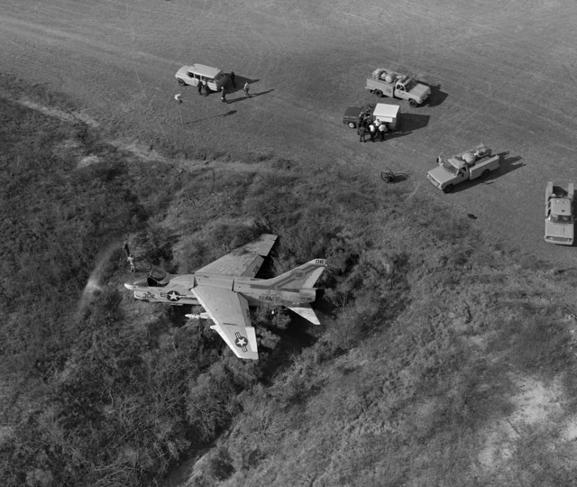 An Attack Squadron 66 (VA-66) A-7E Corsair II aircraft rests in the field where it crash landed. The aircraft suffered moderate damage to its undercarriage and structural damage to its main airframe when it made a crash landing