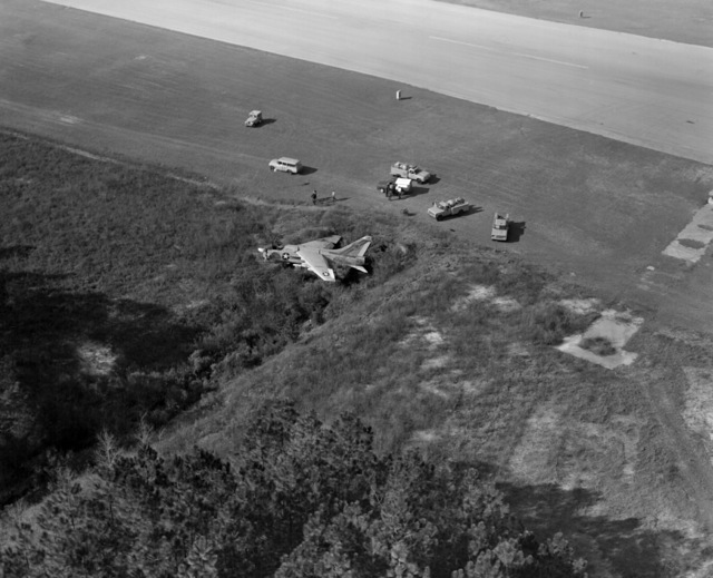 An Attack Squadron 66 (VA-66) A-7E Corsair II rests in the field where it made a crash landing. The aircraft suffered moderate damage to its undercarriage and structural damage to its main airframe when it made a crash landing