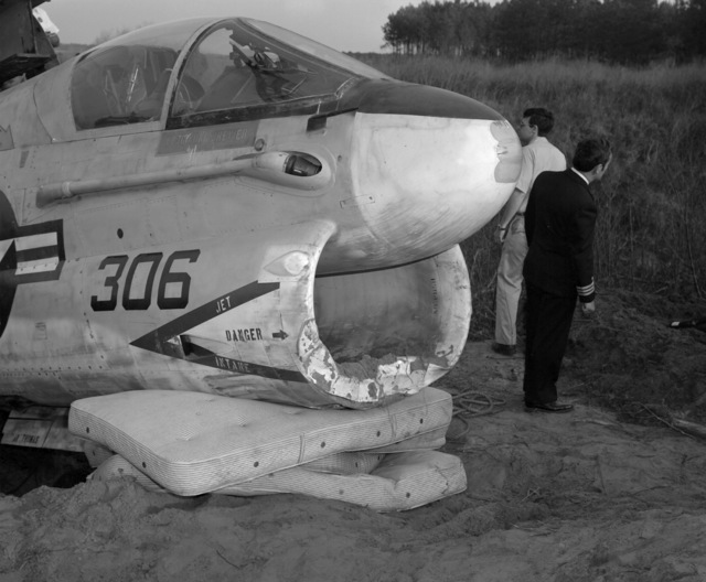 Bed mattresses are used to cushion the nose section of an Attack Squadron 66 (VA-66) A-7E Corsair II during recovery operations. The aircraft suffered moderate damage to its undercarriage and structural damage to its main airframe when it made a crash landing