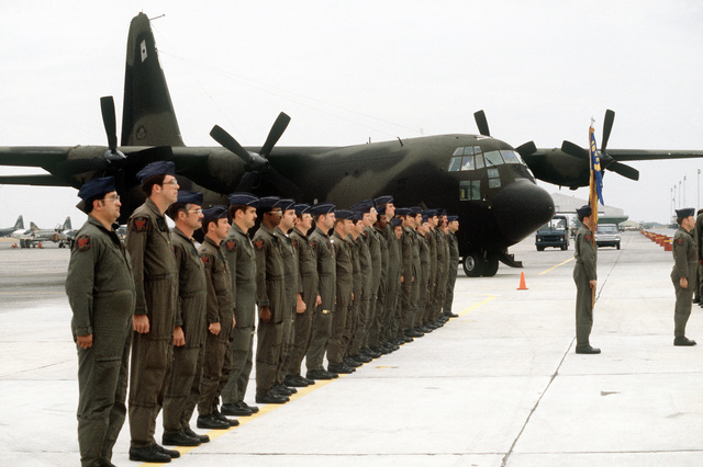 Members of the 1ST Special Operations Squadron stand in front of their MC-130E Hercules aircraft while listening to a welcoming speech. The Squadron has just transferred from Kadena Air Base, Japan
