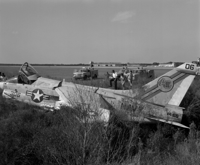 Personnel examine an Attack Squadron 66 (VA-66) A-7E Corsair II during recovery operations. The aircraft suffered moderate damage to its undercarriage and structural damage to its main airframe when it made a crash landing