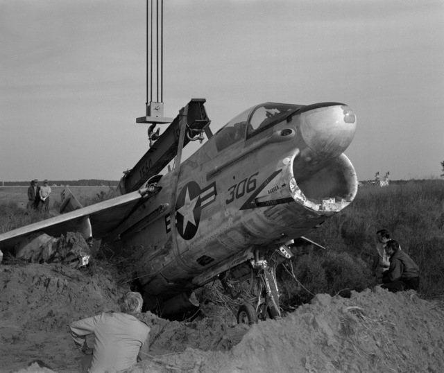Personnel prepare cables which will be used to hoist an Attack Squadron 66 (VA-66) A-7E Corsair II during recovery operations. The aircraft suffered moderate damage to its undercarriage and structural damage to its main airframe when it made a crash landing