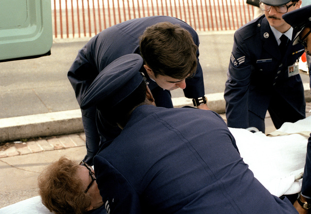 An Air Force medical team prepares to put a stretcher patient into an ambulance. During the parade on Inauguration Day, a few people became ill and needed medical assistance