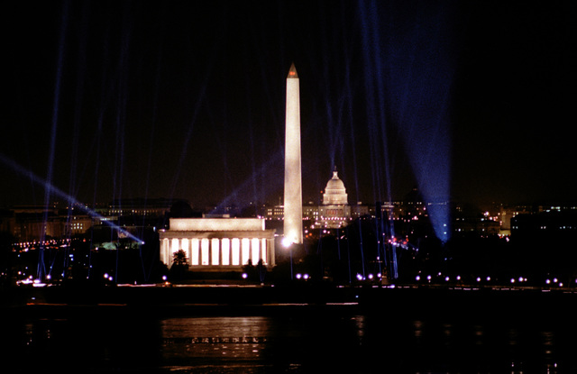 Night scene of the Lincoln Memorial, the Washington Monument and the U.S. Capitol with high beam spotlights pointed at the sky. This scene brought the Inauguration Day celebration to a close