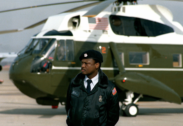 On Inauguration Day an Air Force security policeman stands guard on the side of one of the presidential helicopters (VH-3A)