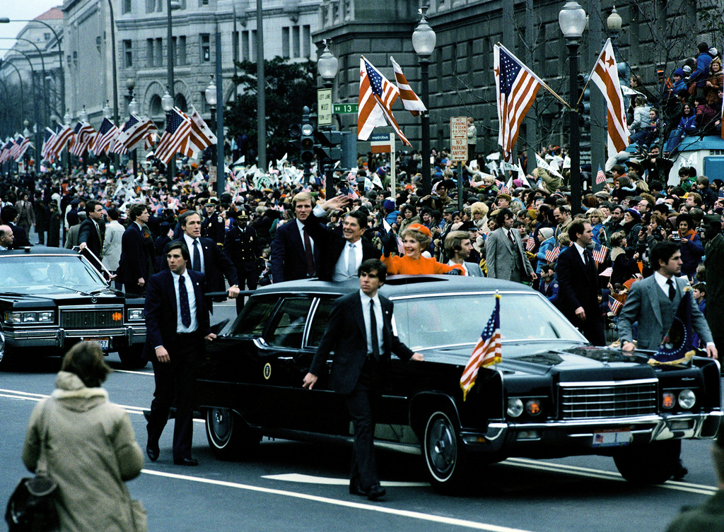 President Ronald Reagan and his wife, Nancy, wave to the public as they ride in the presidential car during the Inauguration Day parade