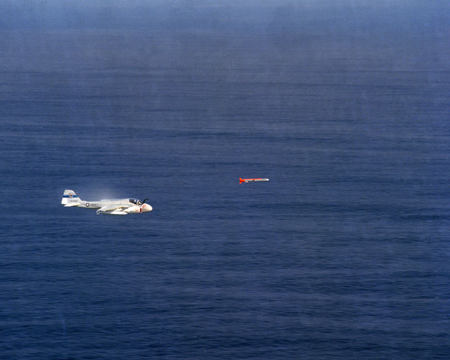 An A-6E Intruder aircraft from the Pacific Missile Test Center observes the test launch of a BGM-109 Tomahawk missile from the nuclear-powered attack submarine USS GUITARRO (SSN 665)