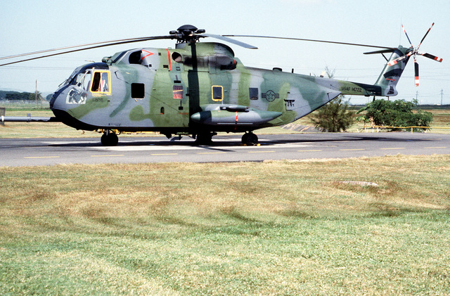 Left side view of a HH-3E Jolly Green Giant helicopter parked on the runway apron