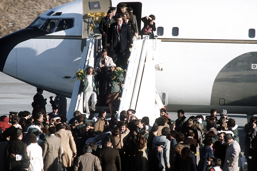 Former hostages to Iran, Bruce Laingen (white coat), Kathyrn Koob and Ann Swift, walk down the plane steps to touch the United States soil for the first time since their release