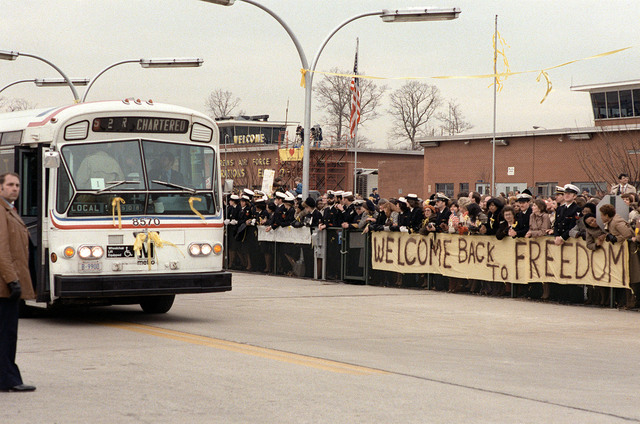 A D.C. public transportation bus with the former Iranian hostages and their families aboard prepares to leave the base for the trip down Suitland Parkway into Washington