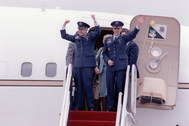 Former Iranian hostages LTC Donald M. Roeder (left), and COL Thomas E. Schaefer pause at the top of the plane steps before continuing down to be welcomed home by Vice President George Bush