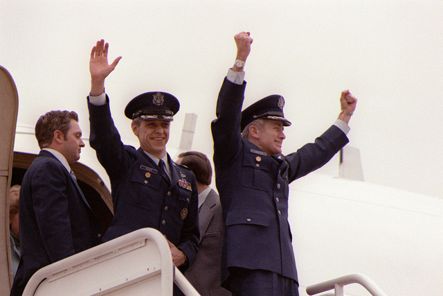 LTC Donald M. Roeder, left, and COL Thomas E. Schaefer wave to the waiting crowd before disembarking from the plane. Roeder and Schaefer are two former Iranian hostages that are en route home after being released