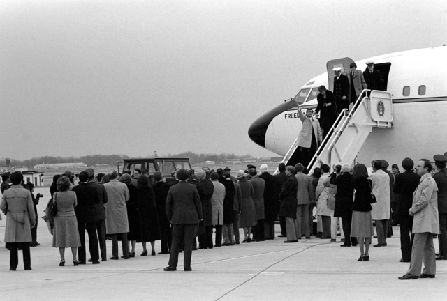 Recently freed Americans held hostage by Iran disembark Freedom One, an Air Force VC-137 Stratoliner aircraft, upon their arrival at the base