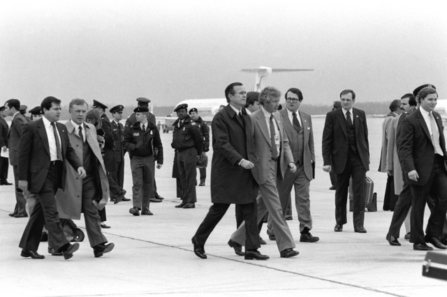 Vice President George Bush and other officials walk toward Freedom One, an Air Force VC-137 Stratoliner aircraft, to welcome the recently freed American hostages held by Iran home