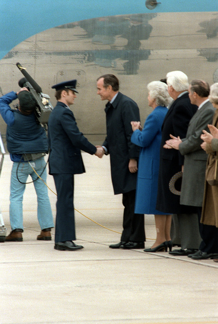 Vice President George Bush shakes hands with former hostage CPT Paul M. Needham to welcome him home after his release from Iran. Behind the Vice President are his wife Mrs. Bush and Speaker of the House Tip O'Neil