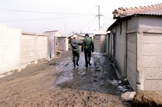 MAJ Saenz, Project Management Office (left), and South Korea Air Force COL Cho walk down a mud street in the Korean village that will be destroyed to provide facilities for the 18 A-10 Thunderbolt II aircraft that will be transferred here