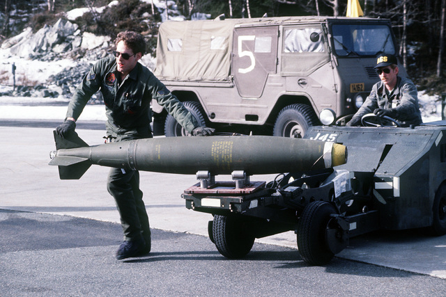 SGT. Jim Hendricks steadies an Mark 82 bomb being carried by a bomb loader to an F-16 Fighting Falcon aircraft for loading
