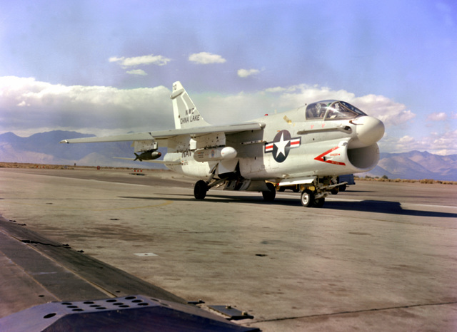 A right front ground view of an LTV A-7E Corsair II aircraft with a HARM instrumentation pod and a Mark 82 practice bomb mounted under its right wing