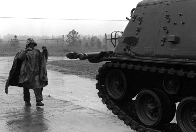 PFC. James Graham guides an M-88 medium recovery vehicle to a parking spot in the tank park