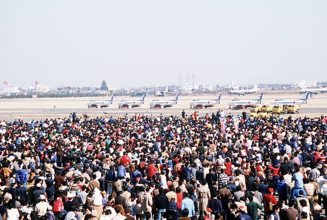 A large crowd watches as five F-86F aircraft from the Japanese Blue Impuse Precision Flying Team taxi out to the runway prior to an air show demonstration flight