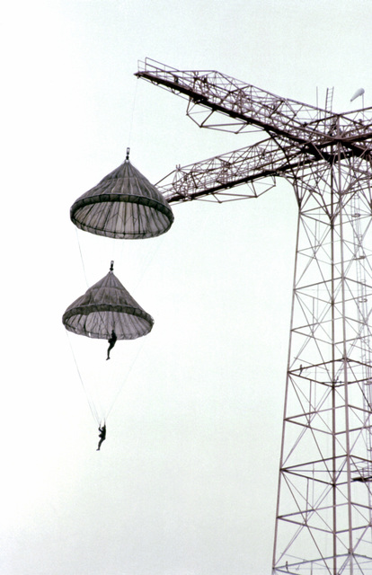 Air Force Reserve flight surgeons hooked to open parachutes are pulled to the top of a 250-foot tower during pararescue training
