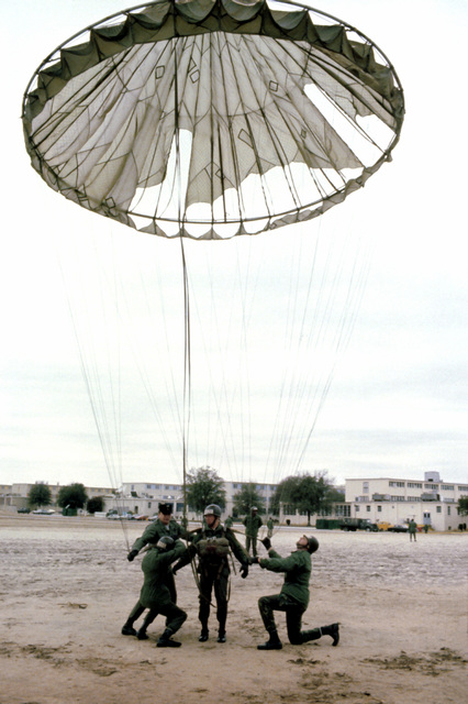 An Air Force Reserve flight surgeon, assisted by the others, is hooked to an open parachute which is to be pulled to the top of a 250-foot tower and released during pararescue training
