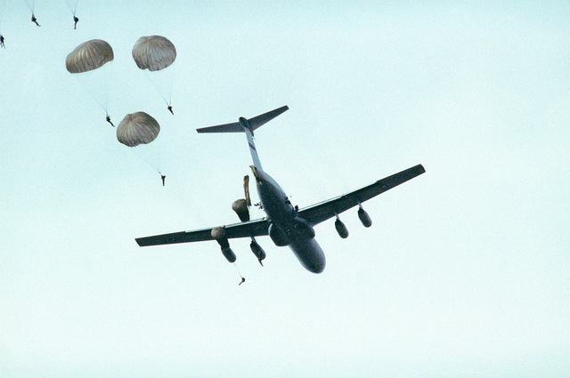 AN air-to-air rear view of a C-141 Starlifter aircraft as it airdrops Air Force Reserve flight surgeons over the Ladson Army Airfield during pararescue training