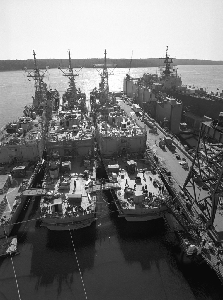 A stern view of the Oliver Hazard Perry class guided missile frigate USS GALLERY (FFG 26), right, at 70 percent completion. Moored to the right, under construction, is the guided missile frigate USS JACK WILLIAMS (FFG 24) and to the left, the guided missile frigate USS CLARK (FFG 11)