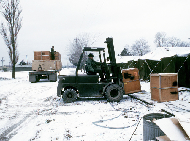 A member of the 554th Civil Engineering Squadron uses a fork lift to unload stoves from a flatbed truck. The stoves will be used in the tent city established for Exercise Team Spirit '81