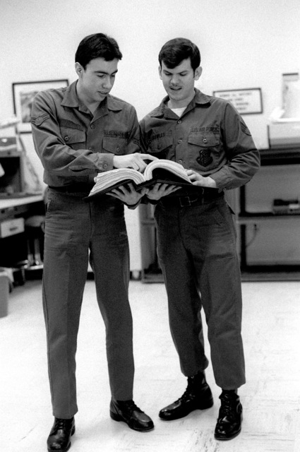 A sergeant and an airman first class of the 1361st Audiovisual Squadron, are dressed in their working uniform. The sergeant is showing the airman how to use on of their specifications manuals