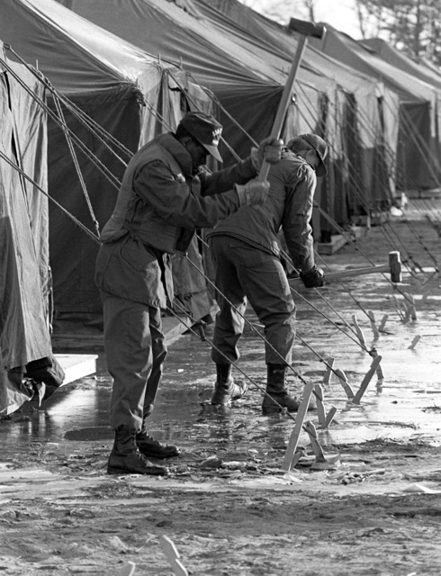 Members of the 554th Civil Engineering Squadron drive in tent stakes, as they erect tents that will be used to house participants in Exercise Team Spirit '81