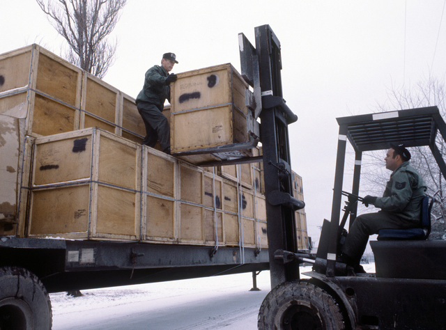 Members of the 554th Civil Engineering Squadron use a fork lift to unload stoves from a flatbed truck. The stoves will be used in the tent city established for Exercise Team Spirit '81