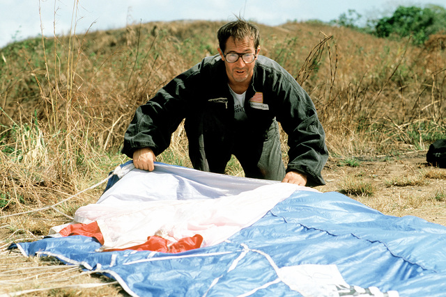 A parachuter begins the task of folding his chutes after a safe landing during exercise Black Hawk IV