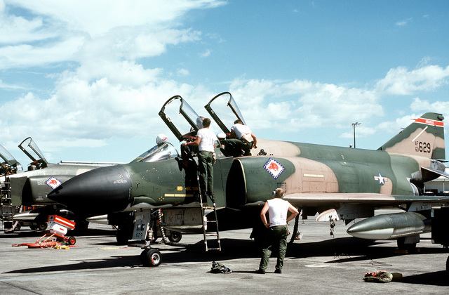 Crew members perform maintenance on an F-4 Phantom II aircraft during exercise Black Hawk IV