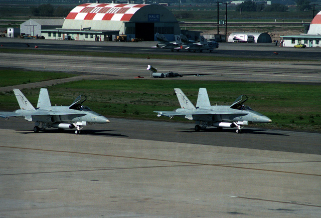 A right side view of two F/A-18 Hornet aircraft from Air Test and Evaluation Squadron Four (VX-4), parked on the runway at Pacific Missile Test Center. Two A-7 Corsair II aircraft, with wings folded, are parked in front of the hangar