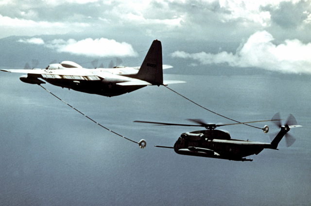 A left rear view of an HC-130P Hercules aircraft refueling a CH-53C Super Jolly helicopter, in flight over the Pacific Ocean