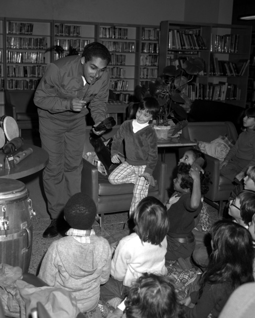 AN airman 1ST class demonstrates African primitive musical instruments to elementary school children during Black History Week