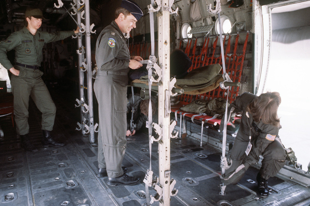 """1ST Aeromedical Evacuation Squadron members erect rig uprights, which will hang """"litter patients"""" in stacks, aboard an aircraft during exercise Team Spirit '81"""