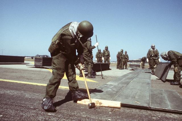8th Civil Engineering Squadron members wearing chemical warfare gear perform rapid runway repair during exercise Team Spirit '81
