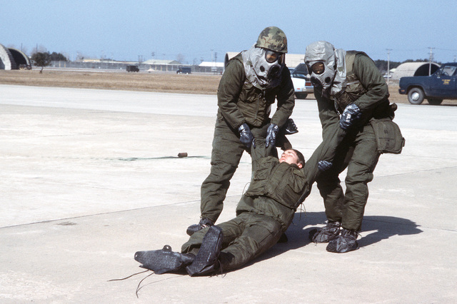 "8th Combat Support Group disaster preparedness team members wearing chemical warfare gear pick up a ""casualty"" during exercise Team Spirit '81"