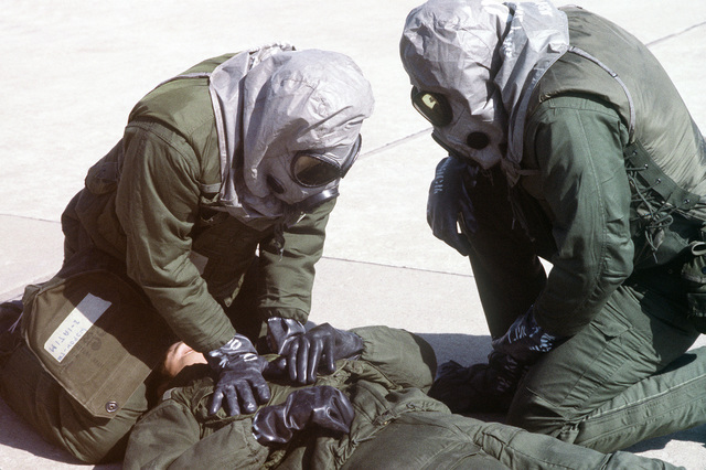 "8th Combat Support Group disaster preparedness team members wearing chemical warfare gear work on a ""casualty"" during exercise Team Spirit '81"