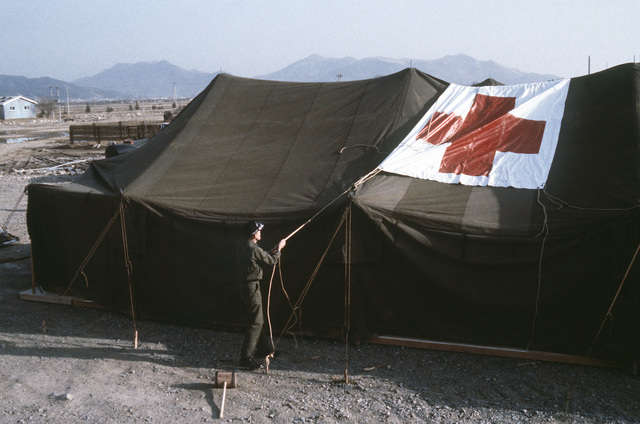A 655th Tactical Field Hospital Squadron member marks a hospital tent with a Red Cross roof sign during exercise Team Spirit '81