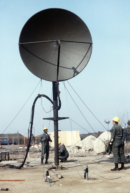 A combat communication group member erects a parabolic TRC-97A radio antenna during exercise Team Spirit '81