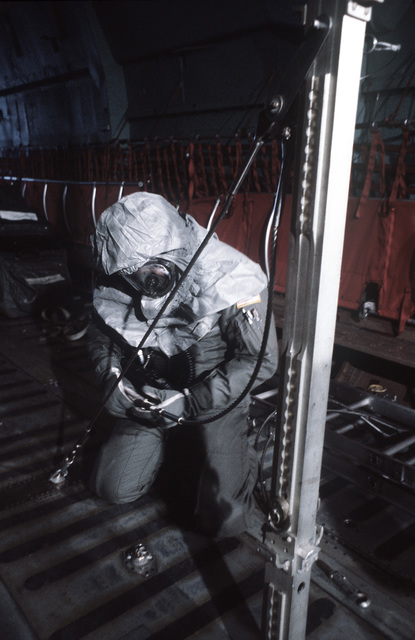 A crewman in protective clothing works to reconfigure a C-141 Starlifter aircraft into a medevac plane during a chemical warfare exercise