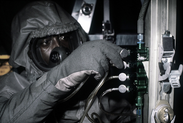 A crewman wearing protective clothing assists in the reconfiguration of a C-141 Starlifter aircraft to serve as a medevac plane during a chemical warfare exercise