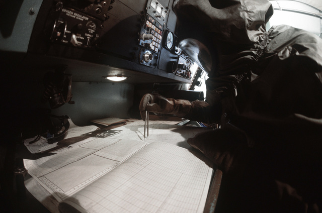 A flight crewman in protective clothing plots a course in the cockpit of a C-141 Starlifter aircraft during a chemical warfare exercise