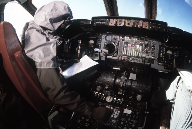 A flight crewman in protective clothing prepares a C-141 Starlifter aircraft for takeoff during a chemical warfare exercise